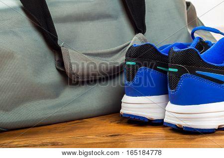 Sport bag sport shoes on wooden floor