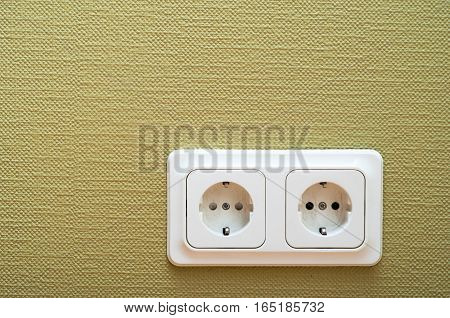 White dual socket on green wall electric