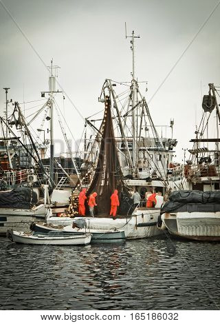 Fisherman crew fixing nets on fishing boat Zadar Croatia