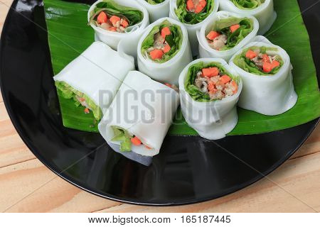 spring roll and vegetable on banana leaf in plate Select focus with shallow depth of field.
