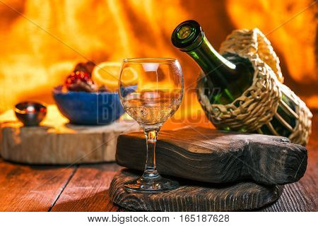 Wine bottle in wicker wrap, sparkling wine in glass and fresh fruit over fire background