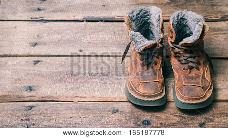 Winter fur lace boots on the wooden floor. Color toning