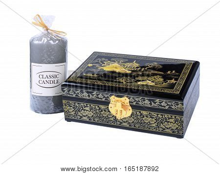Picture of the wooden jewel-box with painting on wood and golden lock near a gray candle isolated on white background. Painted pattern on closed box for bijouterie. Side view.