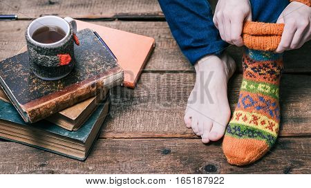 Female feet and hands putting on warm winter sock on the wooden floor next to books stack and mug of tea. Closeup view