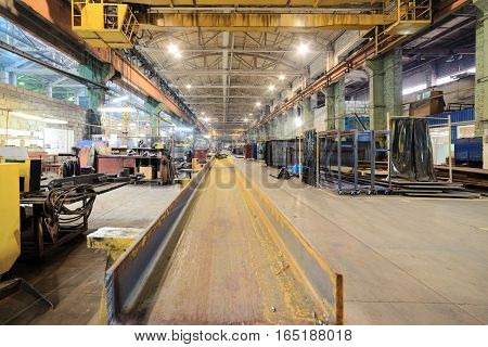 Rusty steel I-beams. Plot welding machine factory.