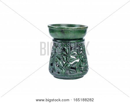 Picture of a green aroma lamp made of stone isolated on white background. Made of stone aroma lamp with floral ornaments.