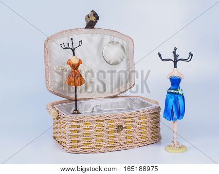 Composition of opened beige-coloured box with two stands for bijouterie isolated on white background. Handmade decoupage box for needlework. Orange mannequin styled stands for bijouterie