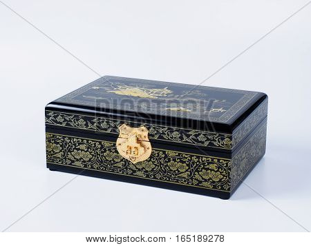 Picture of the wooden jewel-box with painting on wood and golden lock on white background. Painted pattern on a closed box for bijouterie. Side view.