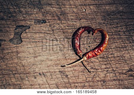Two Chili Peppers Forming A Shape Of Heart On Old Wooden Background. Love Valentine Concept.