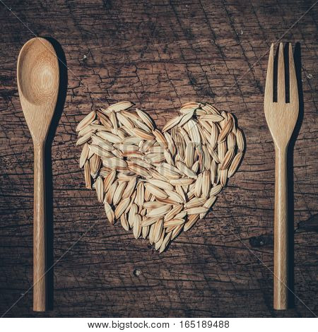 Paddy Heart Symbols  With Spoon And Fork On Old Wooden Background. Love Organic Food Concept.