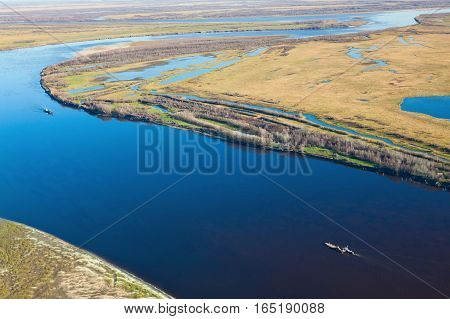 Aerial view of the ship which is pushing barge with vehicle details on the great river in autumn.