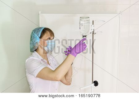 The nurse prepares an IV for intravenous infusion