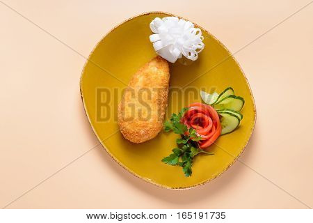 Traditional Kiev-style cutlet on dish decorated with vegetables