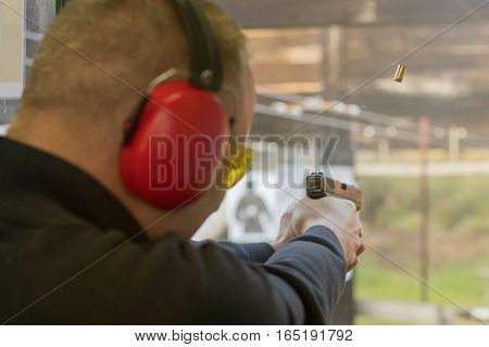 Shooting With A Pistol. Man Firing Pistol In Shooting Range.