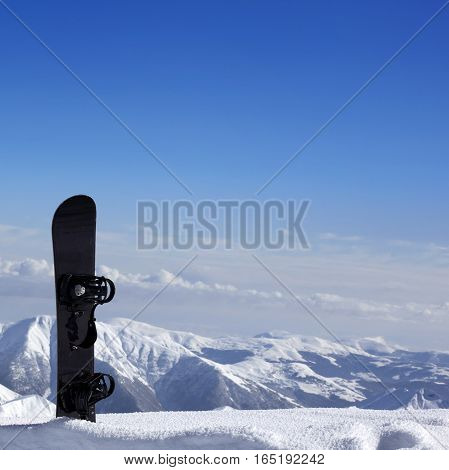 Snowboard In Snow Near Off-piste Slope In Sun Day