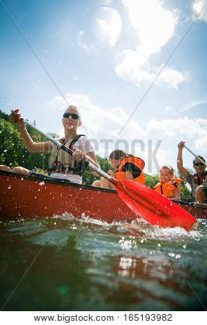 young family in a canoe on the neckar river in germany.