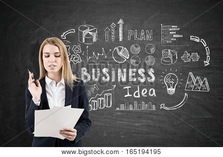 Thoughtful blond businesswoman reading a document is standing near a blackboard with business idea icons