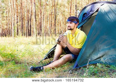 Guy sitting near the tent in the forest and drinking tea