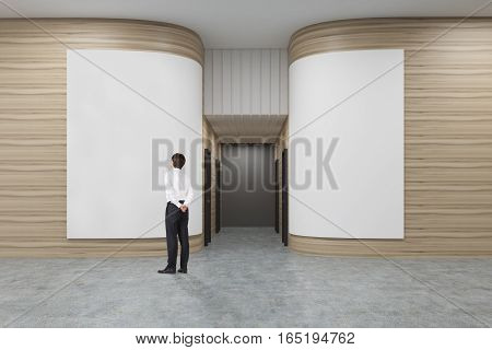 Rear view of a businessman in a white shirt looking at a poster in an office hall with rounded wooden walls. Rows of doors are leading to an elevator. 3d rendering. Mock up