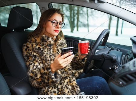 Beautiful woman in a fur coat with red lips sending a text message and drinking coffee while driving