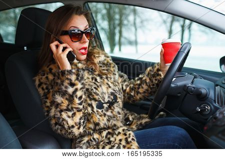Beautiful woman in a fur coat with red lips multitasking while driving drinking coffee and talking on the phone