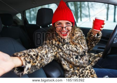 Funny woman in a fur coat and red hat with red lips with coffee to go talking with someone while driving her car