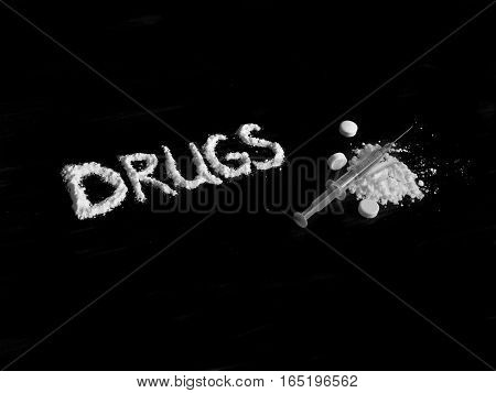Cocaine drug powder in drugs word shaped, injection syringe on cocaine powder pile and pills on black background in black and white colors