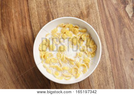 corn flakes with milk in white bowl on wood table directly above, simple healthy breakfast