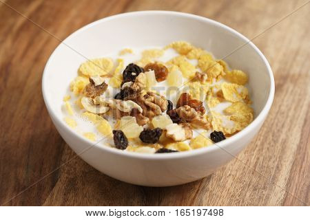 corn flakes with fruits and nuts in white bowl on wood table, simple healthy breakfast