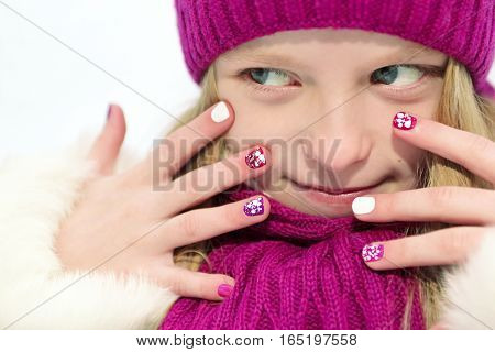 Children's winter mixed colors manicure with glitter under the snow the girl in the cherry hat and scarf on a white background.