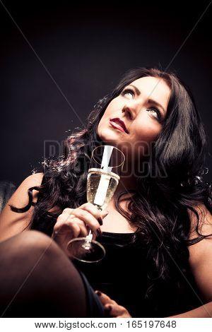 Studio shot of young woman enjoying a glass of champagne