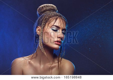 Beautiful blonde young woman with braids hairdo and blue bright makeup covered in water drops. Eyes closed. Studio beauty shot. Copy space.