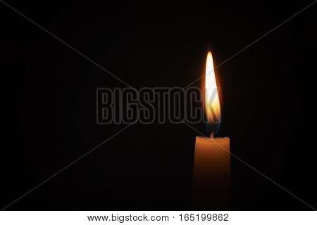 tall candle blown in the dark environment, shallow focus