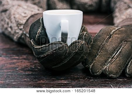 Human hands in winter sheep skin gloves holding cup of coffee. Front closeup view