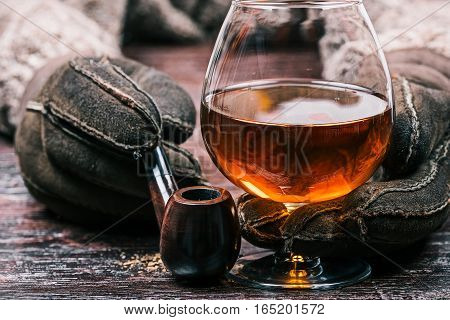 Human hands in winter sheep skin gloves holding glass of brandy and smoking pipe. Front closeup view