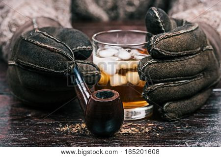 Human hands in winter sheep skin gloves holding glass of wiskey and smoking pipe. Front closeup view