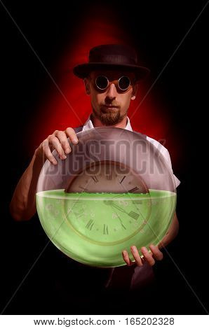 Bearded man in hat holding glass sphere with green liquid and clock