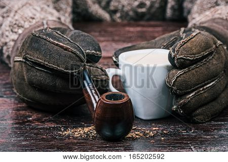 Human hands in winter sheep skin gloves holding cup of coffee and smoking pipe. Front closeup view