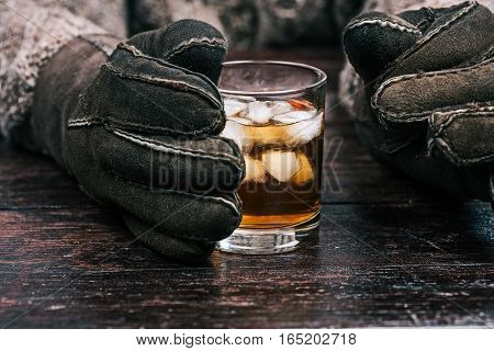 Human hands in winter sheep skin gloves holding glass of wiskey. Front closeup view