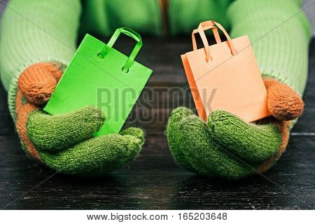Human hands in bright-colored winter gloves holding tiny shopping bags. Concept of fast delivery or gifts to everyone