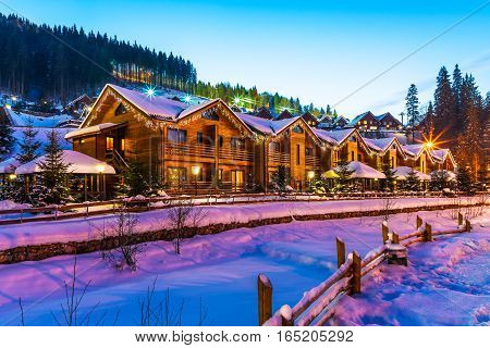 Scenic winter view of mountain ski resort with snowy house cottages with forest and skiing in Bukovel, Ukraine