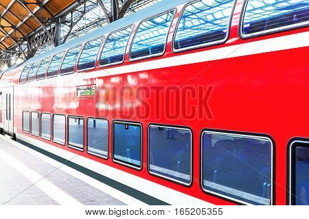 Modern red high speed electric passenger commuter double deck train at station platform