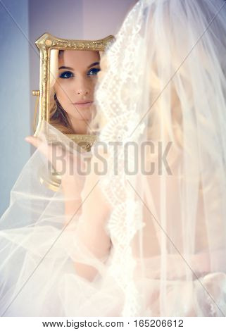 beautiful bride in a veil admiring themselves in the mirror. The reflection in the mirror