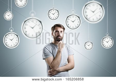 Bearded man in a gray T-shirt is standing and thinking in a room with hanging giant pocket watches. Gray background.