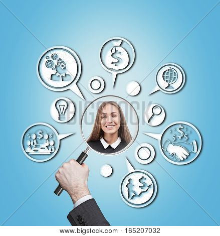 Portrait of a young smiling woman and a man's hands with a magnifying glass. Round business and money icons against blue background. Concept of recruitment