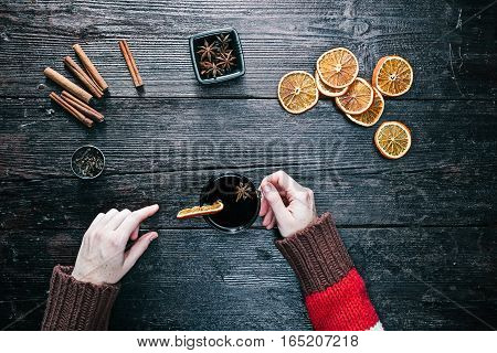 Female hands holding a cup of spiced tea. Overhead view