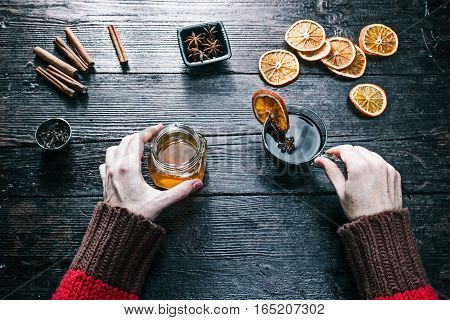 Female hands holding a jar of honey and a cup of tea. Overhead view