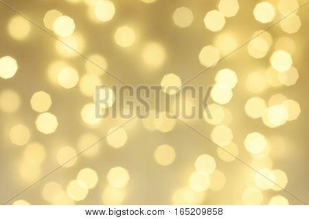 Abstract gold sparkle background, defocused Christmas bokeh. Shimmering blur spot lights, defocussed golden lights with copy space