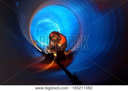 A worker is doing the pipe welding on the pipeline construction