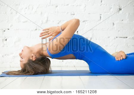 Young attractive woman practicing yoga, stretching in Fish exercise, variation of Matsyasana with lotus legs pose, Namaste, working out, wearing sportswear, blue suit, indoor, white studio background